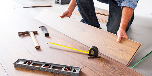 Professional installer installing hardwood flooring planks