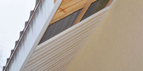 Eave of a house with white vinyl soffit and fascia being installed
